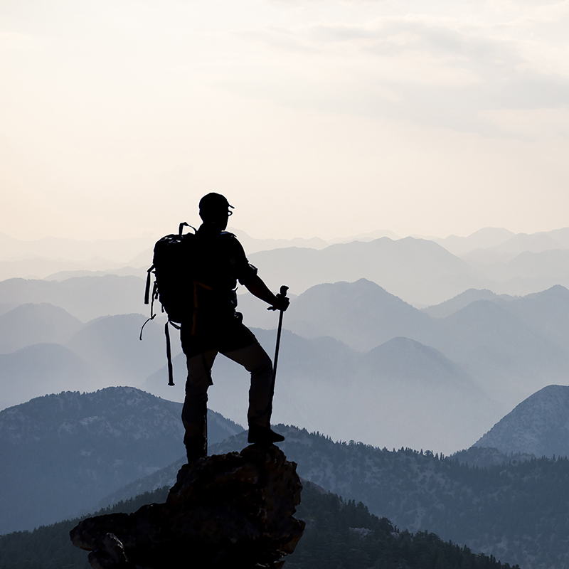 man climbing tall mountain and looking at view