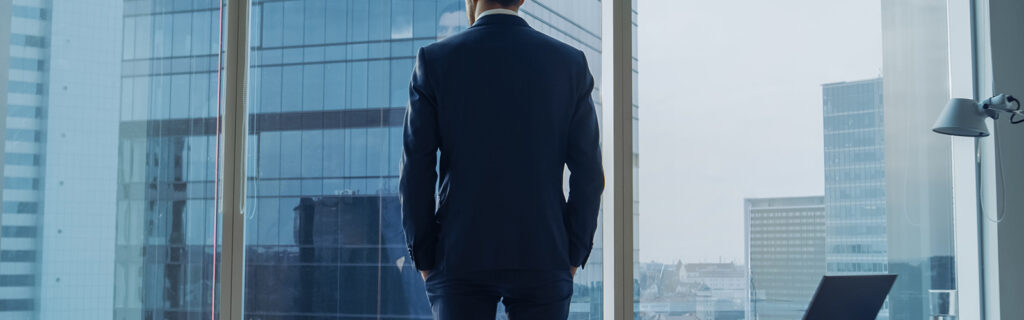 wealthy man staring out highrise corporate building