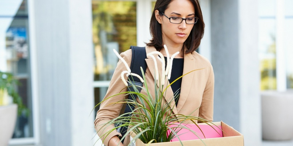 woman carring box with plant from office