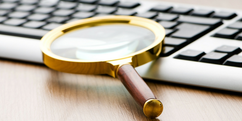 magnifying glass resting on keyboard